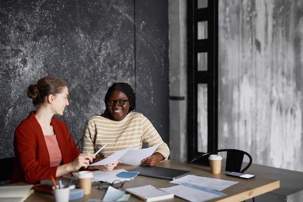 Портрет двух успешных деловых женщин, обсуждающих проект за столом в сером офисе, копией пространства