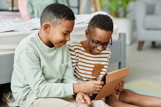 Портрет двух афроамериканских мальчиков-подростков, вместе использующих цифровой планшет в уютной комнате для копирования
