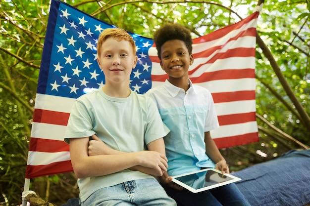 Портрет двух мальчиков-подростков на открытом воздухе, скрывающихся под ветвями большого дерева в лесу или играя на заднем дворе
