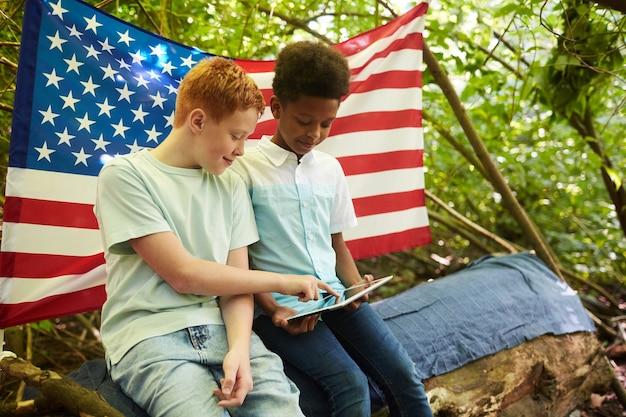 Портрет двух мальчиков-подростков, использующих цифровой планшет на открытом воздухе, прячась под ветвями большого дерева в лесу или играя на заднем дворе
