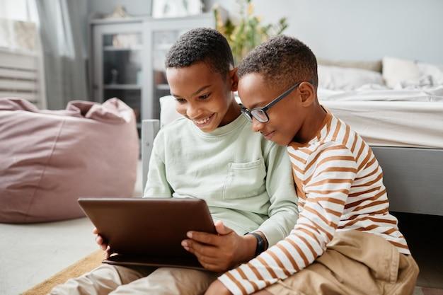 Портрет двух мальчиков-подростков, вместе использующих планшет, сидя на полу дома и смотря видео ...