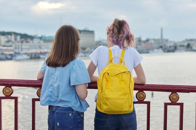 Портрет двух девочек-подростков, стоящих спиной на мосту через реку, подруги, наслаждаясь закатом на поверхности воды, разговаривая, расслабляясь. дружба, образ жизни, молодость, подростки