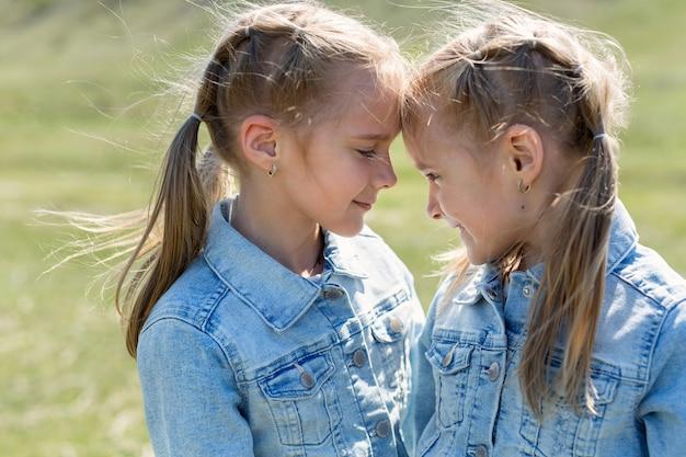 서로 포옹하고 바라 보는 두 쌍둥이 자매의 초상화.