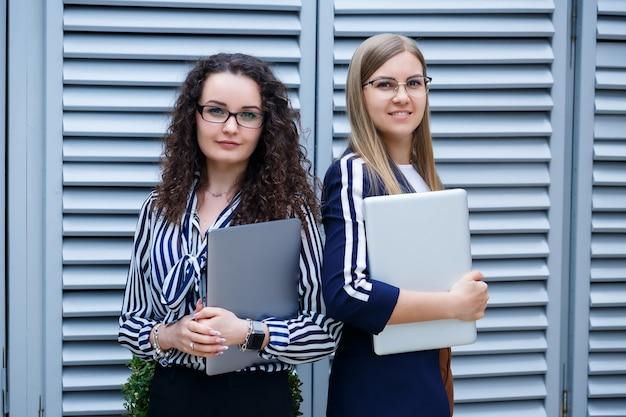 새로운 프로젝트인 노트북을 손에 들고 서 있는 두 여성 사업가의 초상화. 젊은 비즈니스 동료들이 사무에 대해 논의합니다. 안경을 쓴 성공적인 여성 매니저. 비즈니스 개념