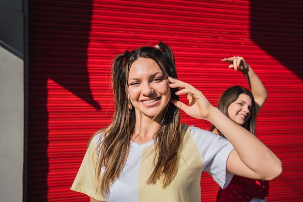 赤い壁の背景で楽しんでいる2人の女性の肖像画