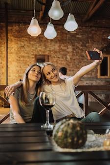 レストランで自分撮りをしている2人の女性の肖像画
