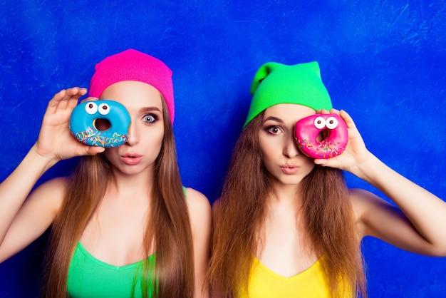 目の近くでドーナツをふくれっ面と保持している2人の女性の肖像画