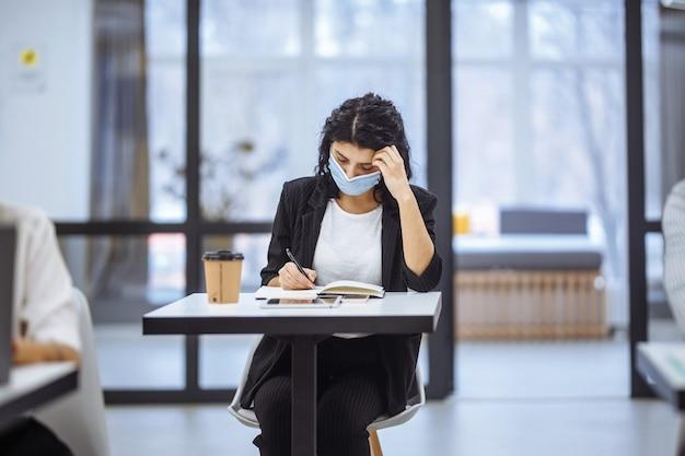 사무실 책상에서 일하고 의료용 마스크를 착용하고 코로나 19 전염병 발생시 안전을 유지하는 두 여성의 초상화.