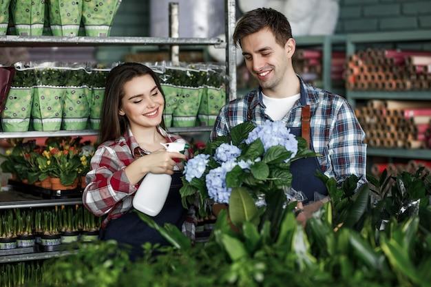 Портрет двух рабочих в специальной одежде, работающих в теплице садового центра