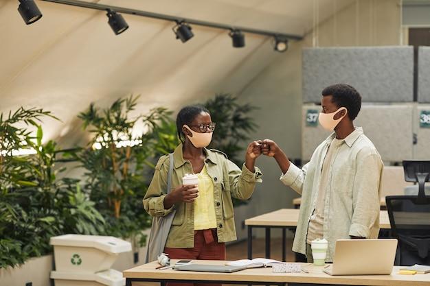 パンデミック後のオフィスで働いている間、非接触型の挨拶として拳をぶつけている2人の若いアフリカ系アメリカ人の肖像画、コピースペース