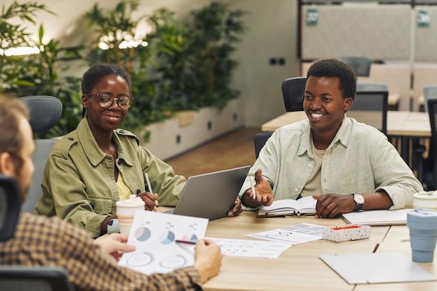 Портрет двух молодых афроамериканцев, улыбающихся коллегам, сидя за столом во время встречи в современном офисе и обсуждения рабочего проекта