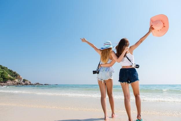 Портрет двух молодых азиатских друзей-друзей, ходить на берегу моря, повернуться обратно в камеру смеется. многорасовые молодые женщины прогуливаются вдоль пляжа.