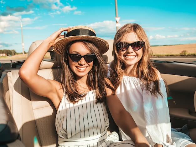 Портрет двух молодых красивых и улыбающихся хипстерских женщин в кабриолете