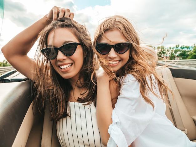 Портрет двух молодых красивых и улыбающихся хипстерских девушек в кабриолете Premium Фотографии
