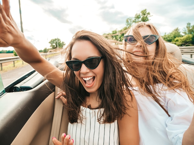 Портрет двух молодых красивых и улыбающихся хипстерских девушек в кабриолете