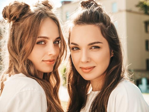 トレンディな夏の白いtシャツの服を着た2人の若い美しい笑顔の流行に敏感な女性の肖像画