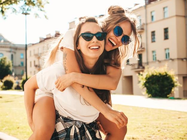 トレンディな夏の白いtシャツの服を着た2人の若い美しい笑顔の流行に敏感な女の子の肖像画