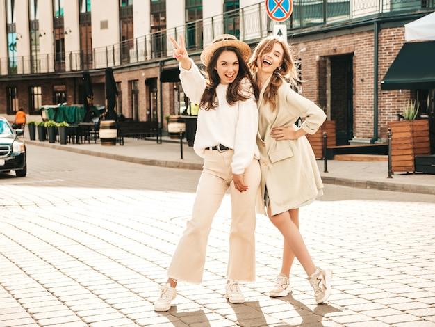 Портрет двух молодых красивых улыбающихся хипстерских девушек в модном белом свитере и пальто