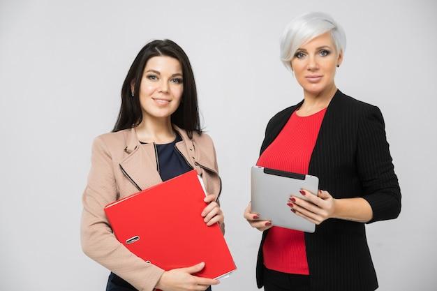 Портрет двух молодых бизнес-леди в костюмах