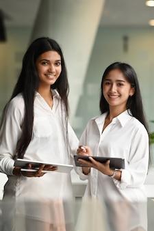会議室に立って笑っている2人の若い実業家の肖像画。