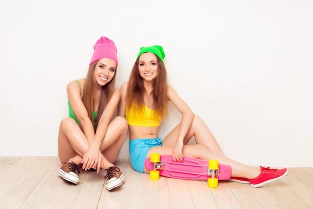 床に座っている2人の若い陽気なスケーターの肖像画