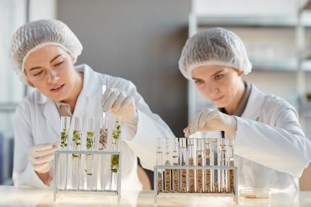 생명 공학 실험실에서 실험을하는 동안 식물 샘플로 테스트 튜브를 사용하는 두 젊은 여성 과학자의 초상화