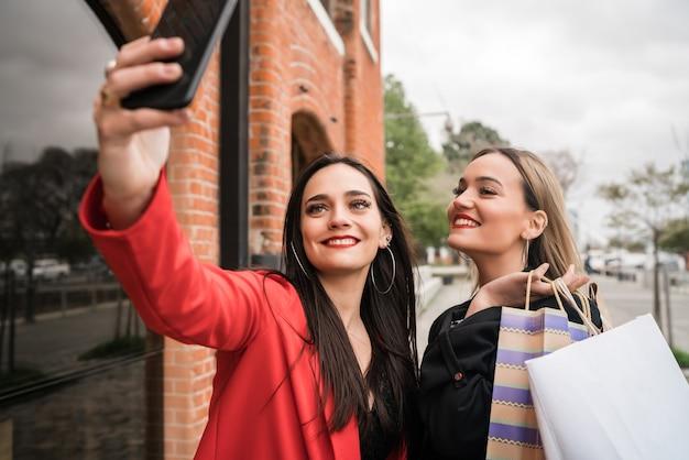 거리에서 전화로 셀카를 복용하는 동안 함께 쇼핑을 즐기는 두 젊은 친구의 초상화