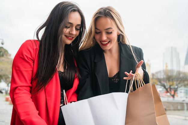 通りを歩きながら一緒に買い物を楽しんでいる2人の若い友人の肖像画。友情とショッピングのコンセプト。