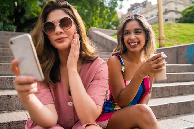屋外の階段に座って一緒に楽しんで携帯電話を使用している2人の若い友人の肖像画。アーバンコンセプト。