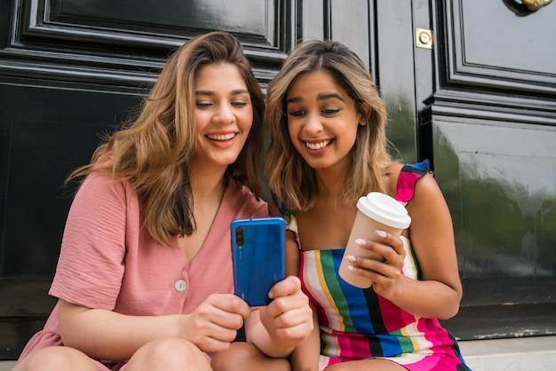 함께 즐기고 야외에 앉아 휴대 전화를 사용하는 두 젊은 친구의 초상화. 도시 개념입니다.