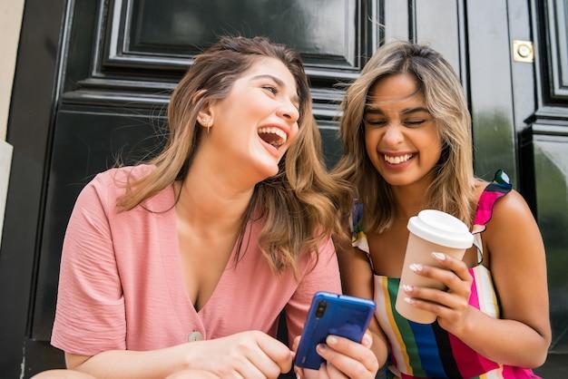 一緒に楽しんで、屋外に座って携帯電話を使用している2人の若い友人の肖像画。アーバンコンセプト。