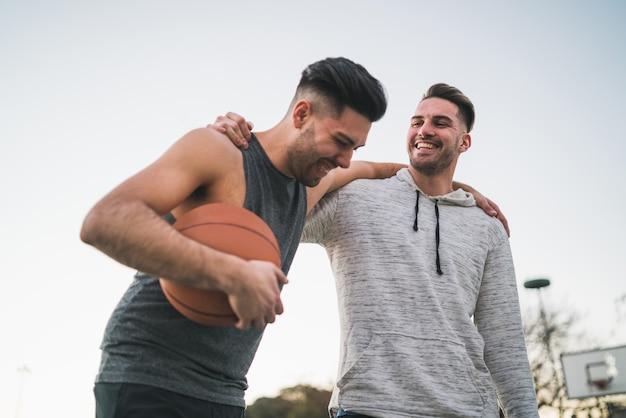 Портрет двух молодых друзей, играющих в баскетбол и весело проводящих время на корте на открытом воздухе. концепция спорта.
