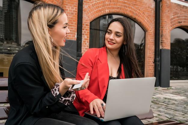 Портрет двух молодых друзей, делающих покупки в интернете с помощью кредитной карты и ноутбука, сидя на открытом воздухе. концепция дружбы и образа жизни.