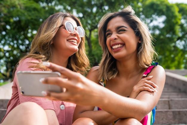 야외에 앉아 웃으면서 휴대폰으로 셀카를 찍는 두 젊은 친구의 초상화. 도시 개념입니다.