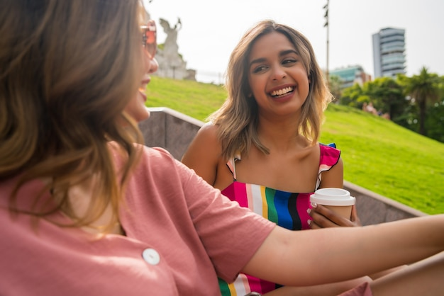 함께 좋은 시간을 보내고 야외 계단에 앉아 이야기를 나누는 두 젊은 친구의 초상화. 도시 개념입니다.
