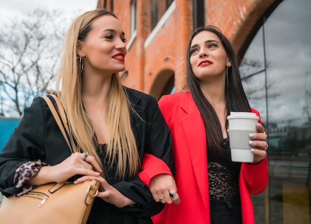 Портрет двух молодых друзей, хорошо проводящих время вместе во время прогулки на свежем воздухе по улице. концепции образа жизни и дружбы.