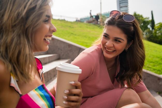 함께 시간을 보내고 야외 계단에 앉아있는 동안 이야기하는 두 젊은 친구의 초상화. 도시 개념.