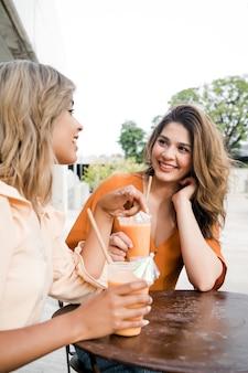 야외 커피숍에서 함께 시간을 보내는 두 젊은 친구의 초상화