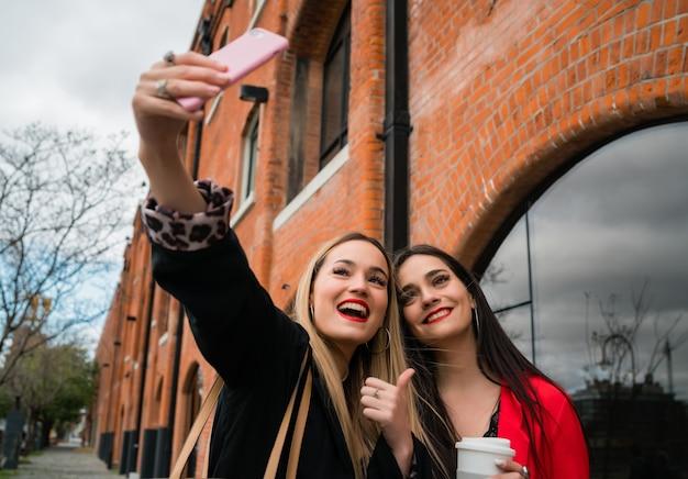 Портрет двух молодых друзей, делающих селфи с мобильным телефоном на улице. концепции образа жизни и дружбы.
