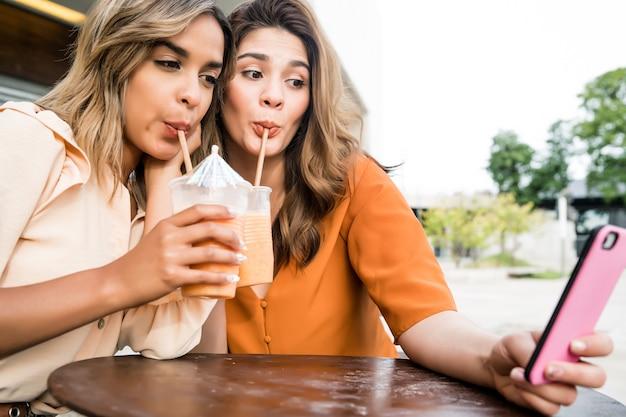 屋外のコーヒーショップで携帯電話で自分撮りをしている2人の若い友人の肖像画。アーバンコンセプト。