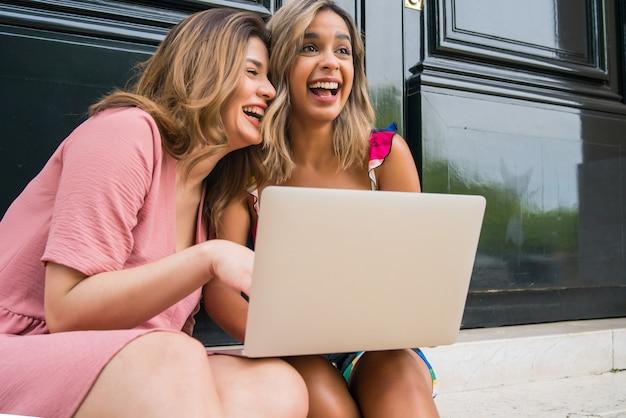 야외에 앉아 노트북을 사용하는 두 젊은 친구의 초상화. 도시 개념입니다. 기술 개념입니다.