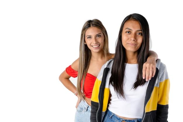 真っ白な背景に2人の若い笑顔のラティーナ女性の友人の肖像画。