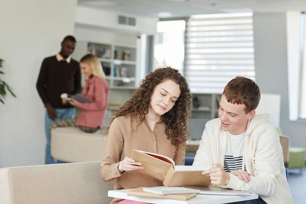대학 도서관의 테이블에 앉아 웃고있는 동안 함께 공부하는 두 젊은 학생 소년 광고 소녀의 초상화,