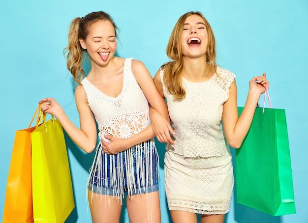 Портрет двух молодых стильных улыбающихся белокурых женщин, занимающих хозяйственными сумками. женщины в летней хипстерской одежде. позитивные модели позируют на синем черном фоне