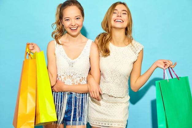 Портрет двух молодых стильных улыбающихся белокурых женщин, занимающих хозяйственными сумками. женщины в летней хипстерской одежде. позитивные модели позируют на синей стене