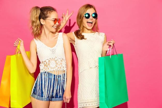Портрет двух молодых стильных улыбающихся белокурых женщин, занимающих хозяйственными сумками. женщины в летней хипстерской одежде. позитивные модели позируют на розовом черном фоне