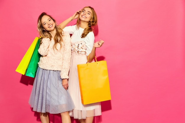 Портрет двух молодых стильных улыбающихся белокурых женщин, занимающих хозяйственными сумками. женщины в летней хипстерской одежде. позитивные модели позируют на розовой стене