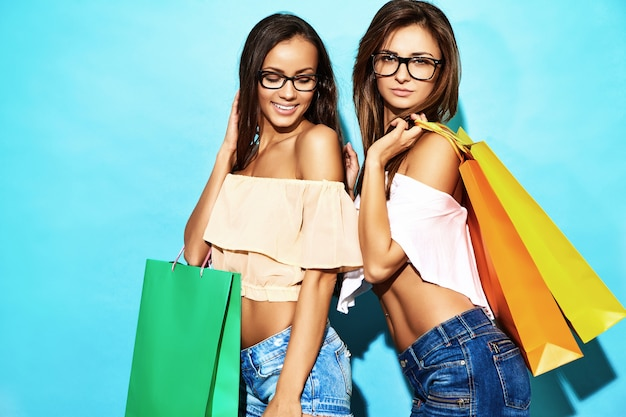 買い物袋を保持している2人の若いスタイリッシュな笑顔ブルネット女性の肖像画。夏の流行に敏感な服を着た女性。青い背景の上にポーズをとってポジティブモデル