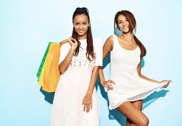 買い物袋を保持している2人の若いスタイリッシュな笑顔ブルネット女性の肖像画。夏の流行に敏感な服を着た女性。青い壁を越えてポーズポジティブモデル