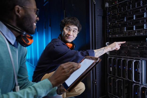 データセンター、コピースペースでの作業中にサーバーネットワークをセットアップする2人の若い技術者の肖像画